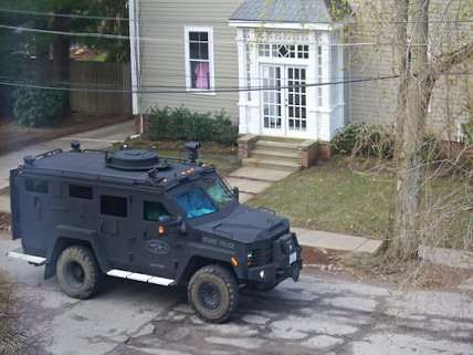 Woman looks on as armored police vehicles rolls down street