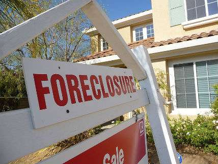 A foreclosure sign hangs in front of a house.