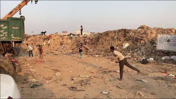 Children play cricket in a trash dump of a Gurgaon slum.