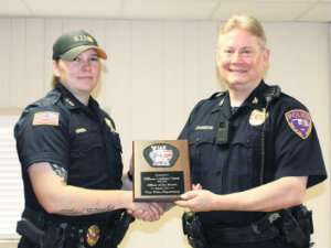 Officer Lindsey Green (left) receives an officer of the month award from Vian Police Chief Ted Johnson