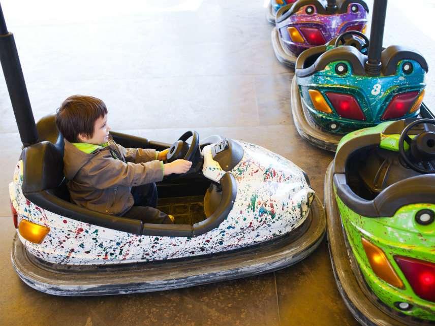 Kid in electric bumper car, amusement park