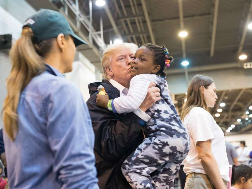 U.S. President Donald Trump holds up a young girl as First Lady Melania Trump looks on during a visit to refugees from Hurricane Harvey the NRG Stadium September 2, 2017 in Houston, Texas.