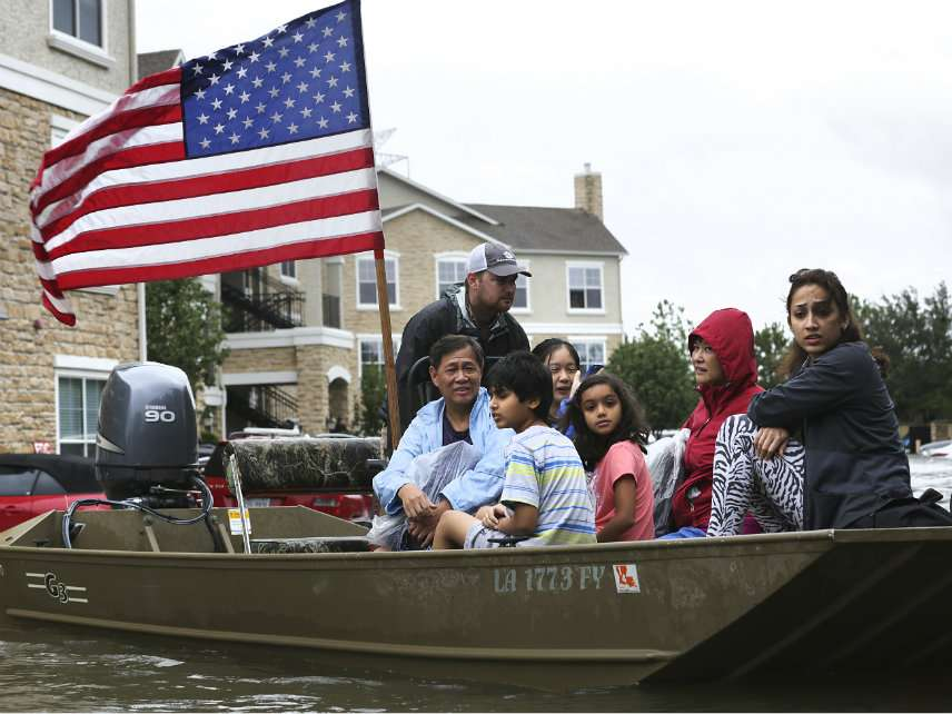 Rescued individuals from the Kelliwood subdivision in Houston are brought in by boat by volunteer rescue workers