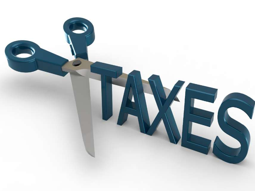 3D concept for scissors cutting the word TAXES