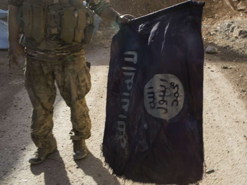 October 17, 2017 - Raqqa, Syria: A member of Syrian Democratic Forces carries an Islamic State flag he just found