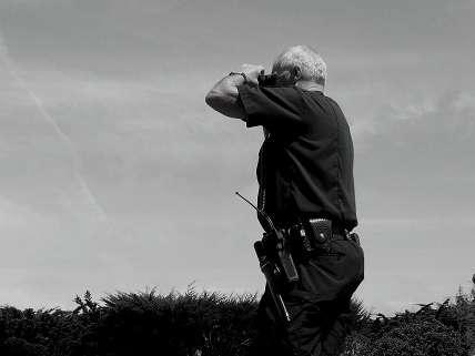 cop looking through binoculars