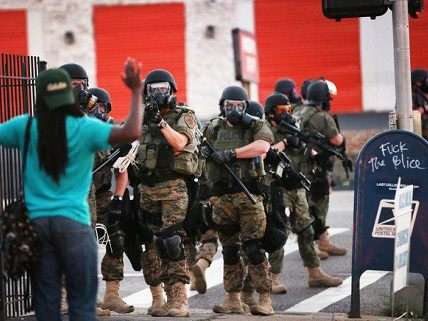 Man holds hands up for SWAT team in Ferguson