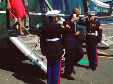 Obama salutes with coffee cup in hand