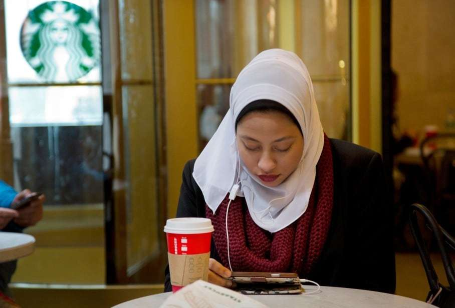 Fifi Youssef pays attention to her iPhone while seated in a Starbucks Coffee, Wednesday, Dec. 16, 2015 in New York. (AP Photo/Mark Lennihan)
