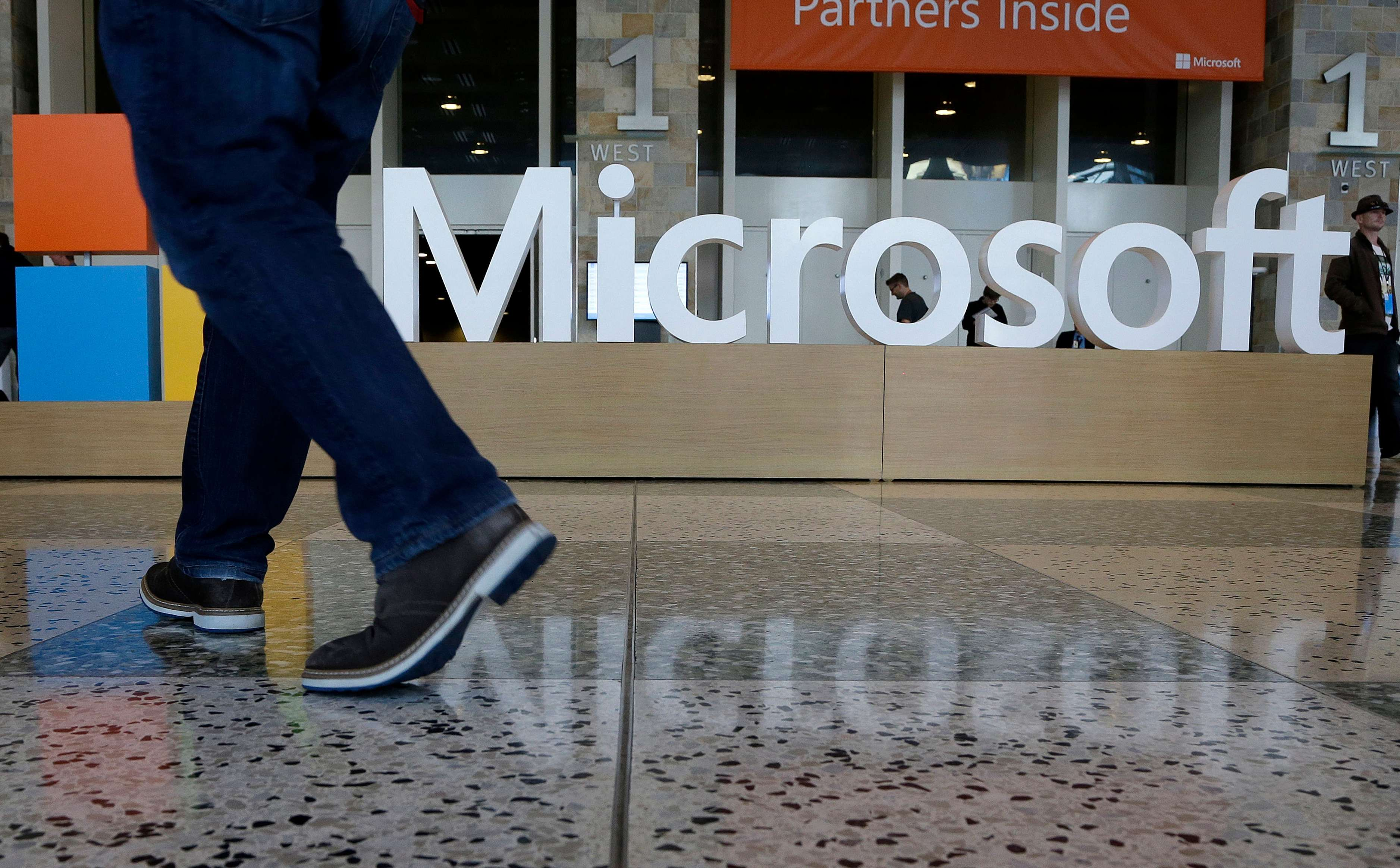In this April 28, 2015 photo, a man walks past a Microsoft sign set up for the Microsoft BUILD conference at Moscone Center in San Francisco. Microsoft reports quarterly financial results after the market close on Tuesday, July 21, 2015. (AP Photo/Jeff Chiu)