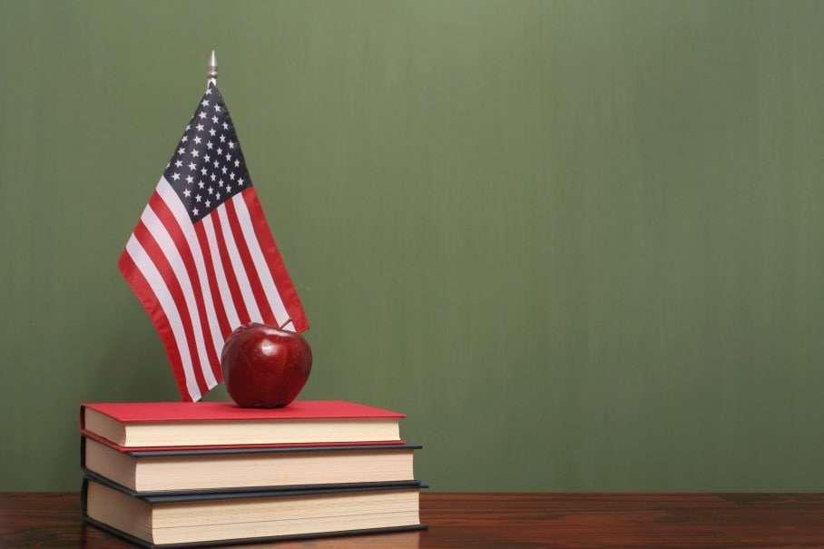 Green chalkboard behind books, apple and American flag. (Sadeugra /iStock)