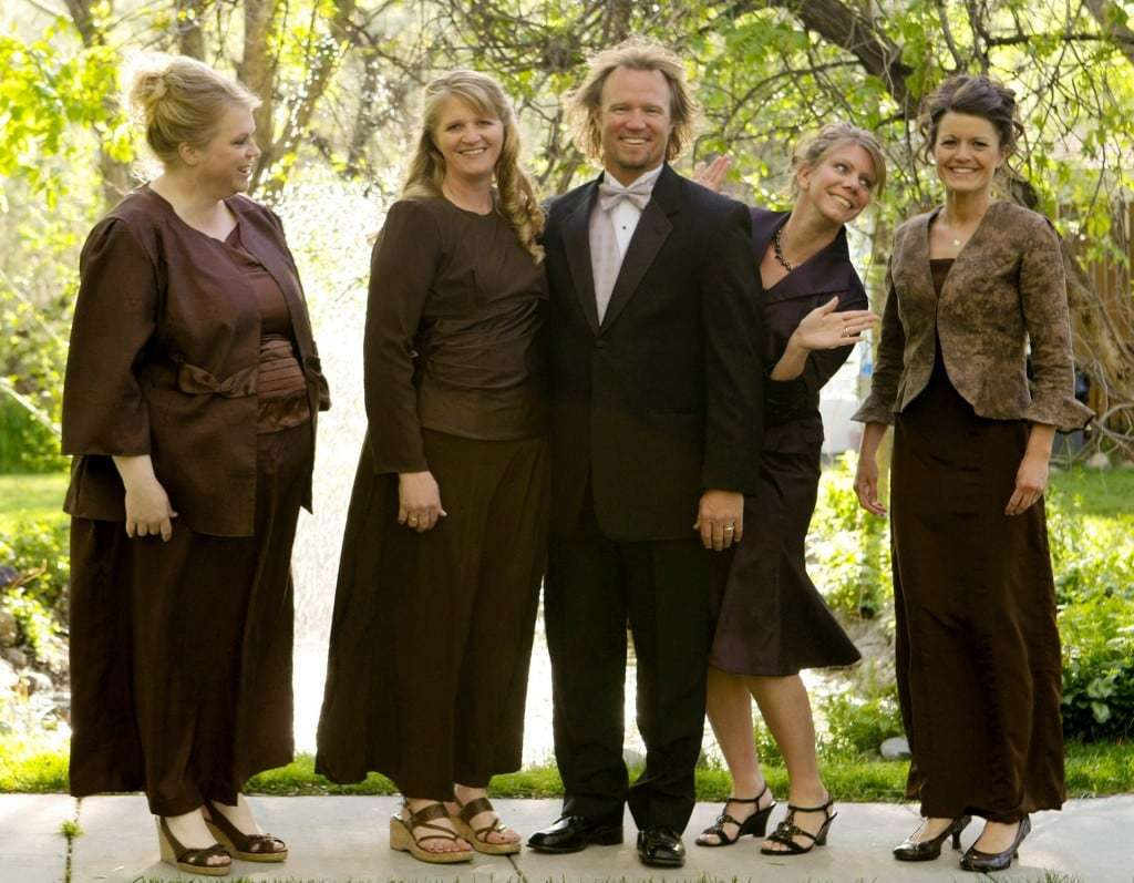 """FILE - In this undated file photo provided by TLC, Kody Brown, center, poses with his wives, from left, Janelle, Christine, Meri, and Robyn in a promotional photo for TLC's reality TV show, """"Sister Wives."""" A Utah county attorney says he will not pursue criminal charges against this polygamous family made famous by a reality TV show. Utah County Attorney Jeff Buhman says he has closed the case against Brown and his four wives. (AP Photo/TLC, Bryant Livingston, File)"""