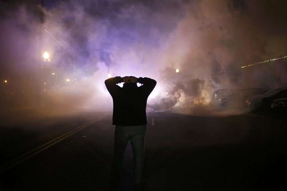 A protester stands with his hands on his head as a cloud of smoke approaches. (Reuters)