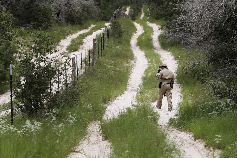 FILE- In this Sept. 5, 2014, file photo, a U.S. Customs and Border Protection Air and Marine agent looks for signs along trail while on patrol near the Texas-Mexico border near McAllen, Texas. A federal judge temporarily blocked President Barack Obama's executive action on immigration Monday, Feb. 16, 2015, giving a coalition of 26 states time to pursue a lawsuit that aims to permanently stop the orders. (AP Photo/Eric Gay, File)