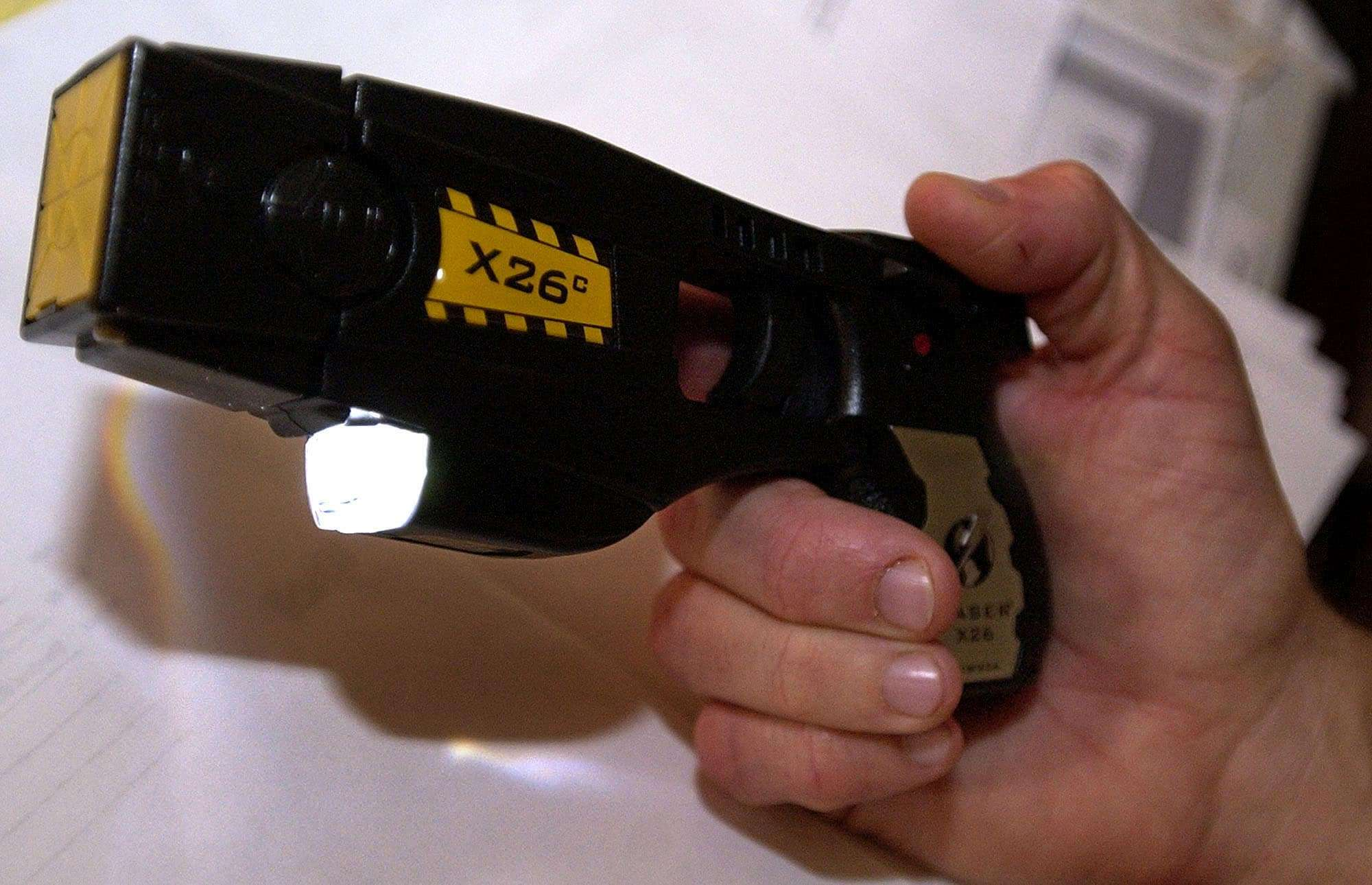 Steve Tuttle, director of communications for Taser International, Inc., holds the X26c stun gun Wednesday, Nov. 24, 2004 at the company's headquarters in Scottsdale, Ariz. The gun is offered to the general public for about $1,000. The company's stock has soared but there are growing concerns about whether the stun guns are truly as non-lethal as advertised. (AP Photo/Tom Hood)