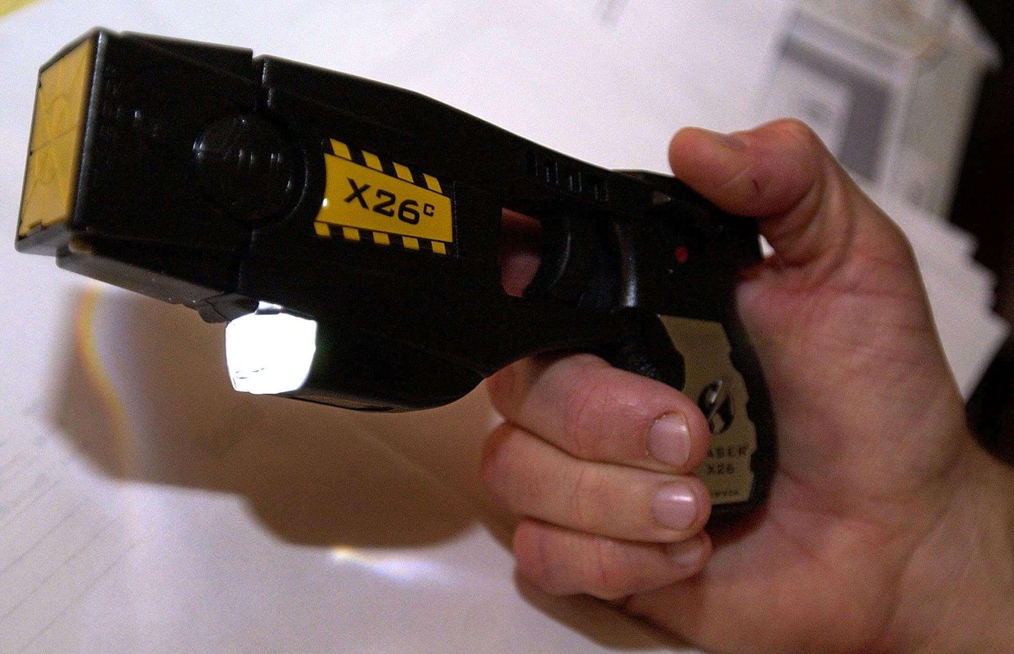 Steve Tuttle, director of communications for Taser International, Inc., holds the X26c stun gun Wednesday, Nov. 24, 2004, at the company's headquarters in Scottsdale, Ariz. (Tom Hood/Associated Press)