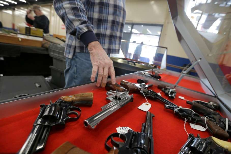 A dealer arranges handguns in a display case before a show in Little Rock, Ark., in this Feb. 6 photo. (AP Photo/Danny Johnston)