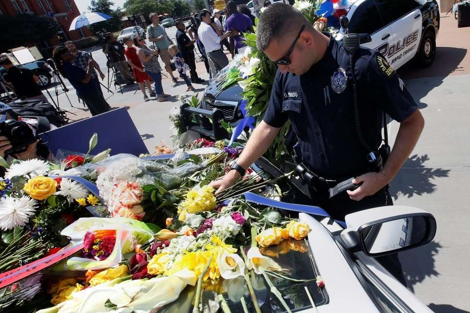 A Dallas police officer observes a moment of silence after putting some flowers on a police car that makes up part of a makeshift memorial at Police Headquarters following the multiple police shooting in Dallas, Texas, U.S.,July 8, 2016. REUTERS/Carlo Allegri