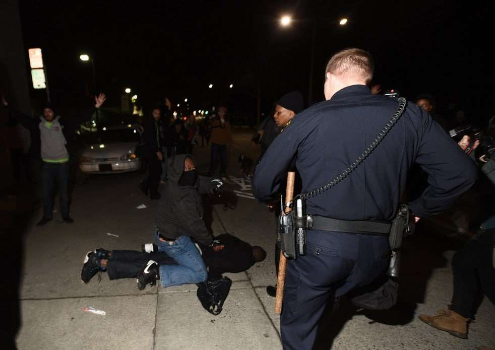 An Oakland Police Department officer (R) approaches as plainclothes California Highway Patrol detectives makes an arrest in Oakland, California December 10, 2014. Chief Avery Browne, commander of the California Highway Patrol's Golden Gate Division, said two plainclothes CHP detectives were surrounded by up to 50 demonstrators who ignored orders to back off, despite one of the officers first taking out his baton and identifying himself as police. Picture taken December 10, 2014. REUTERS/Noah Berger (UNITED STATES - Tags: CIVIL UNREST CRIME LAW) ATTENTION EDITORS: PICTURE 10 OF 10 PICTURES FOR A PICTURE AND ITS STORY PACKAGE 'DETECTIVE'S GUN DRAWN IN OAKLAND' SEARCH 'OAKLAND GUN' FOR ALL IMAGES